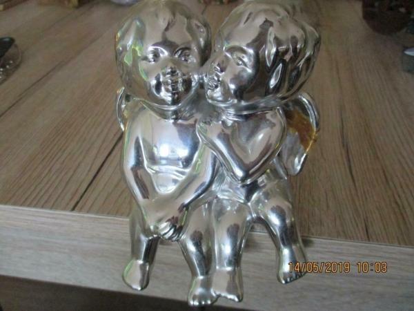 Zilveren kleur engelen beeld van keramiek, zittend afgebeeld